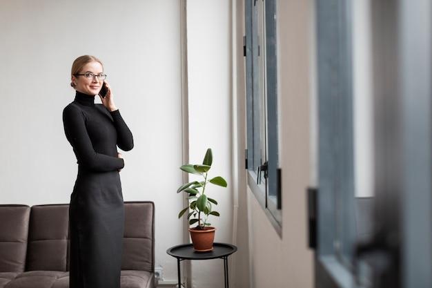 Vista lateral moderna fêmea falando por telefone