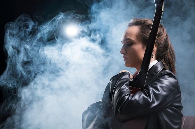 Vista lateral mulher abraçando a guitarra e palco de fumaça