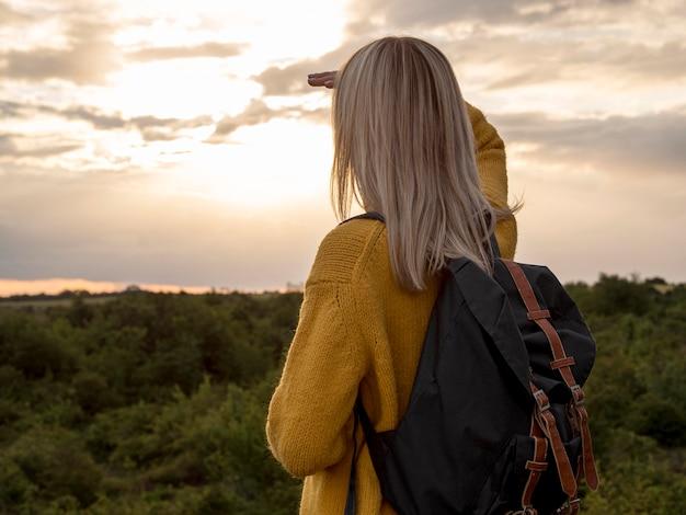 Vista lateral mulher ao pôr do sol na montanha