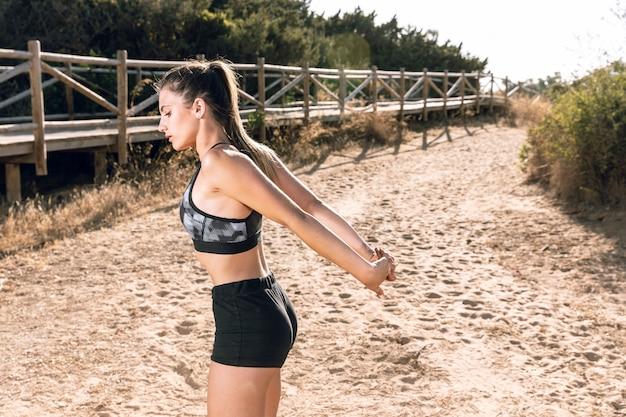 Vista lateral, mulher, aquecer, ligado, areia