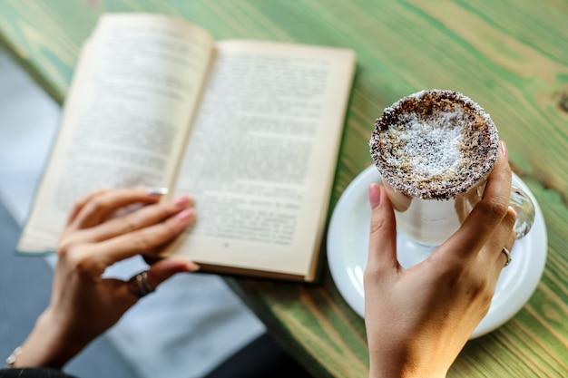 Vista lateral mulher bebendo café com coco e lendo um livro na mesa