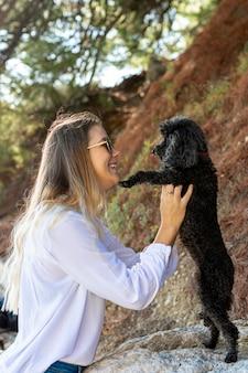 Vista lateral mulher brincando com poodle