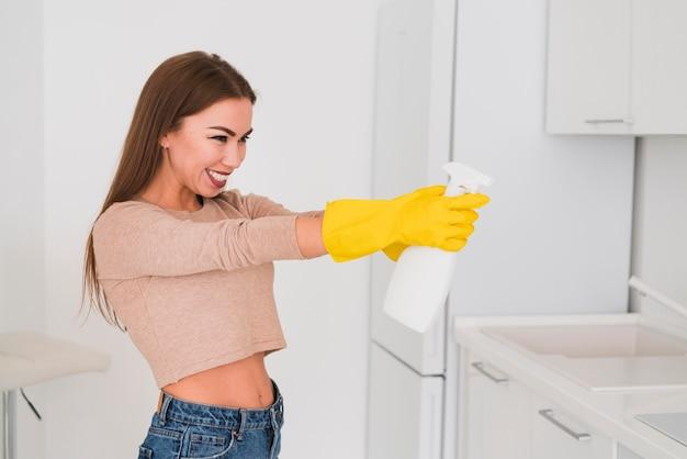 Vista lateral mulher brincando com um frasco de spray