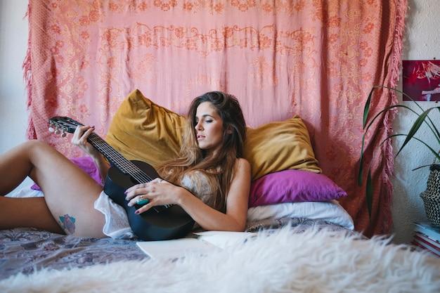 Vista lateral, mulher, brincando, ukulele, cama