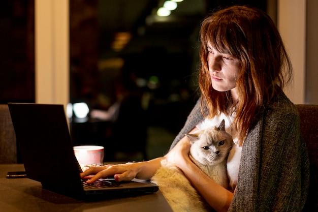 Vista lateral mulher cansada com gato e laptop