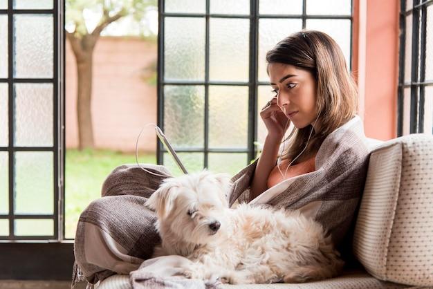 Vista lateral mulher com cachorro no sofá