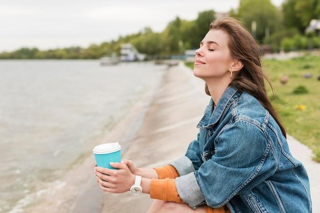 Vista lateral mulher com café à beira-mar