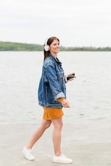 Vista lateral mulher com celular e fones de ouvido