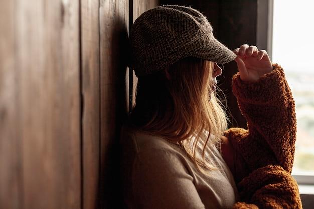 Vista lateral mulher com chapéu posando dentro de casa