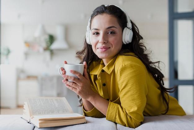 Vista lateral mulher com copo e fones de ouvido
