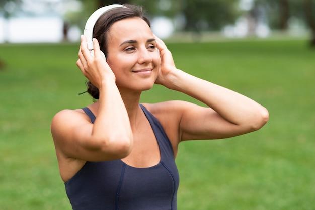 Vista lateral mulher com fones de ouvido ao ar livre
