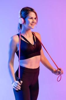 Vista lateral mulher com fones de ouvido de treinamento
