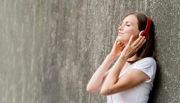 Vista lateral mulher com fones de ouvido