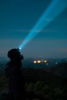 Vista lateral mulher com lanterna de cabeça