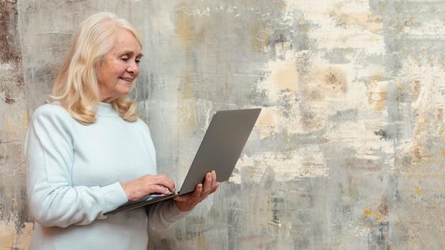 Vista lateral mulher com laptop em casa