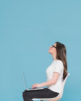 Vista lateral mulher com laptop no colo