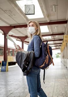 Vista lateral mulher com máscara na estação de trem