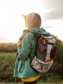 Vista lateral mulher com mochila ao pôr do sol