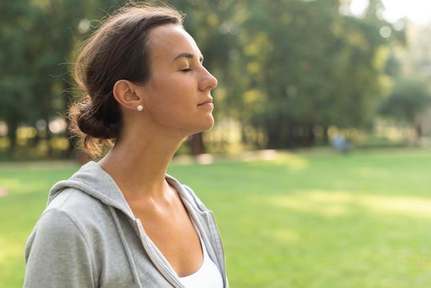 Vista lateral mulher com os olhos fechados ao ar livre