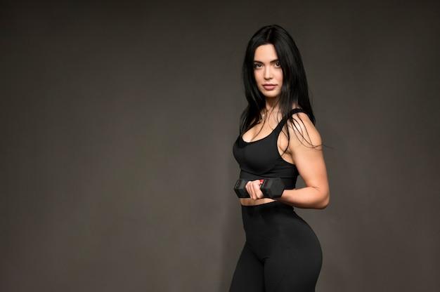 Vista lateral mulher com pesos de mãos