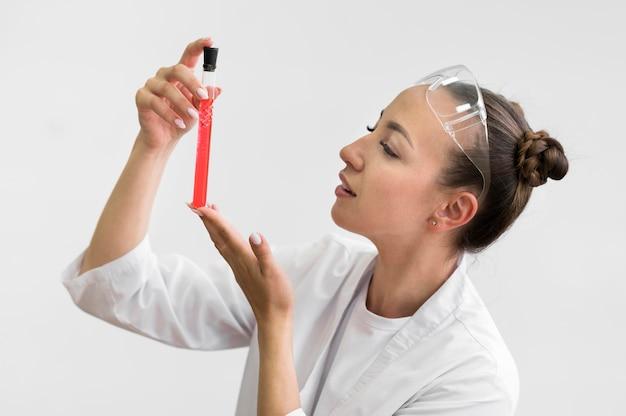 Vista lateral mulher com tubo de ciência