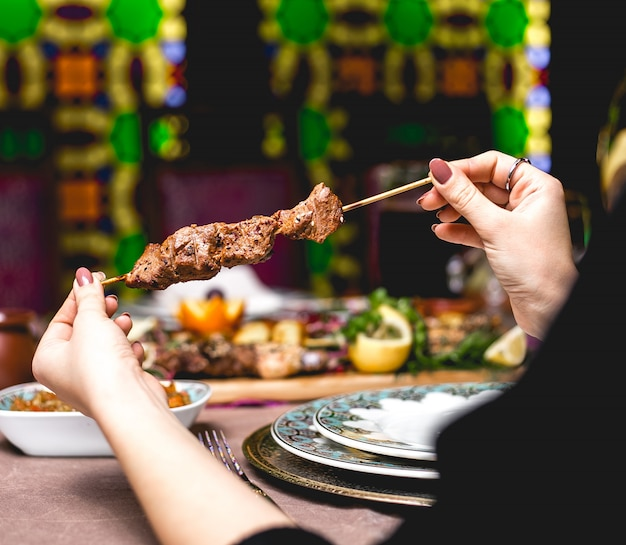 Vista lateral mulher come carne de quibe no espeto