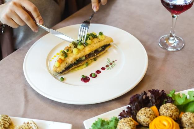 Vista lateral mulher comendo peixe frito com purê de batatas e legumes em um prato