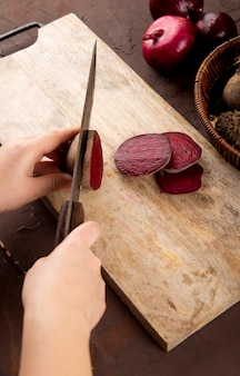 Vista lateral mulher corta beterraba em um quadro negro com beterraba fresca em uma cesta com cebolas vermelhas