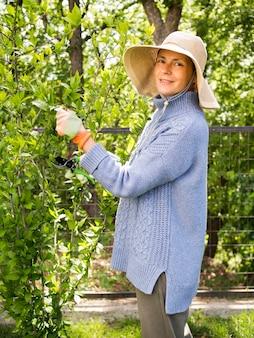 Vista lateral, mulher, corte folhas