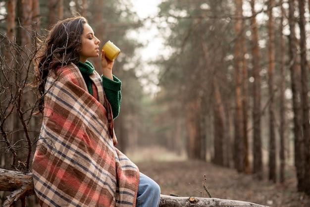 Vista lateral mulher desfrutando de uma xícara de chá na natureza