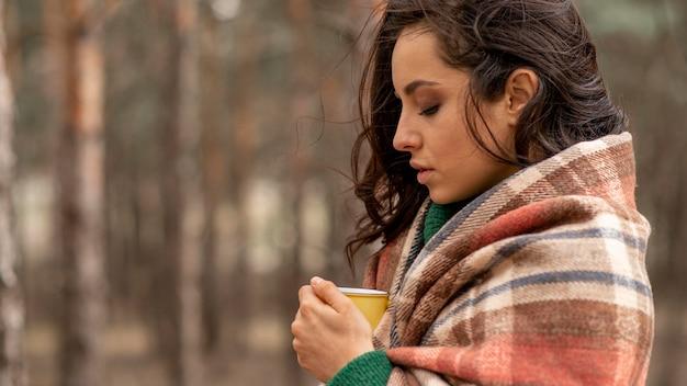 Vista lateral mulher desfrutando de uma xícara de chá