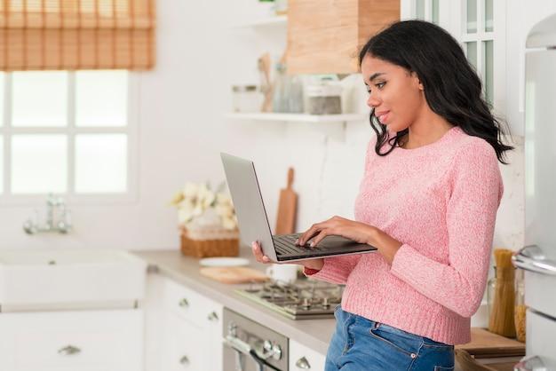 Vista lateral mulher em casa com o laptop