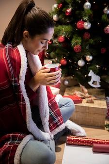 Vista lateral mulher em casa segurando a xícara de te