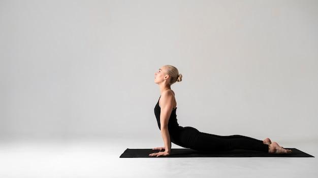 Vista lateral mulher em roupas pretas com tapete de ioga