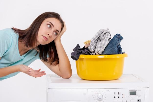Vista lateral mulher entediada perto de cesto de roupa suja