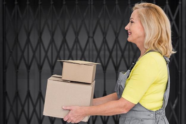 Vista lateral mulher entregando pacotes