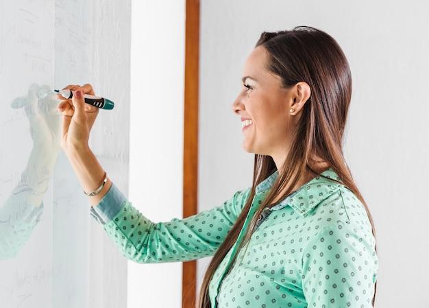 Vista lateral, mulher, escrita, ligado, whiteboard