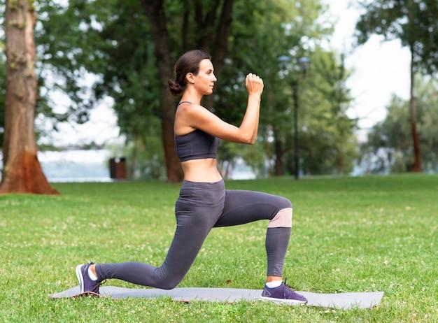 Vista lateral mulher exercitando ao ar livre