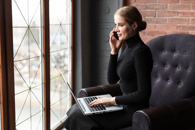 Vista lateral mulher falando no telefone