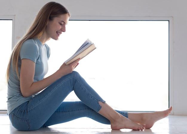 Vista lateral mulher lendo um livro ao lado da janela