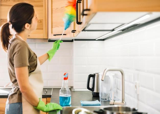 Vista lateral mulher limpando com espanador