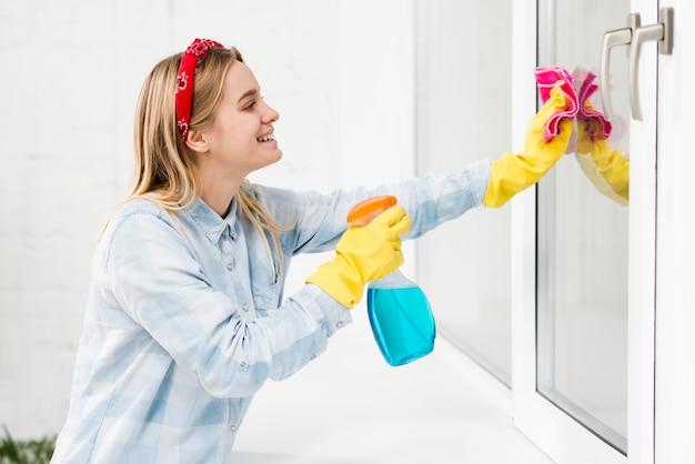 Vista lateral mulher limpando janelas