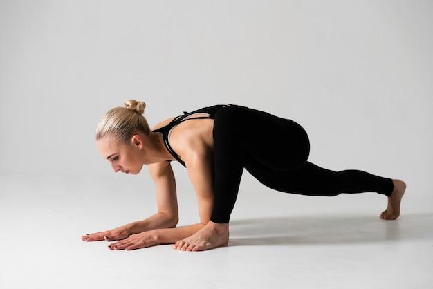Vista lateral mulher loira fazendo yoga