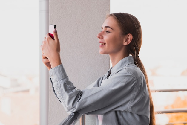 Vista lateral mulher loira usando telefone