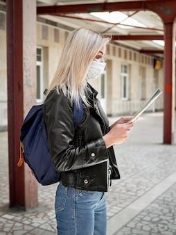 Vista lateral mulher na estação de trem