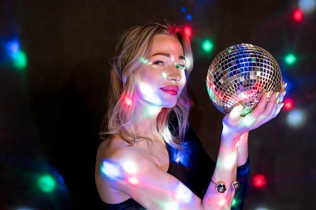 Vista lateral mulher na festa com globo