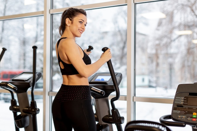 Vista lateral mulher no ginásio na bicicleta