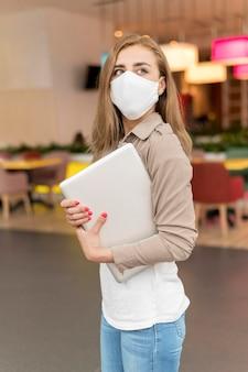 Vista lateral mulher no shopping com laptop usando máscara