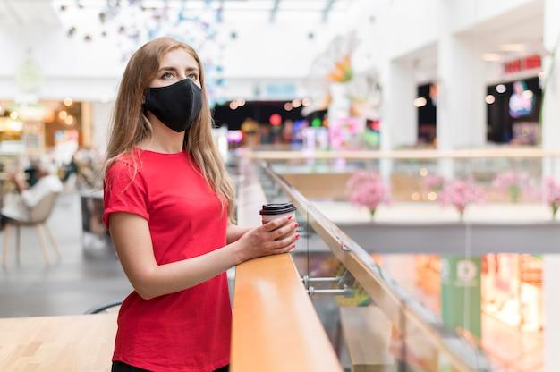 Vista lateral mulher no shopping com máscara