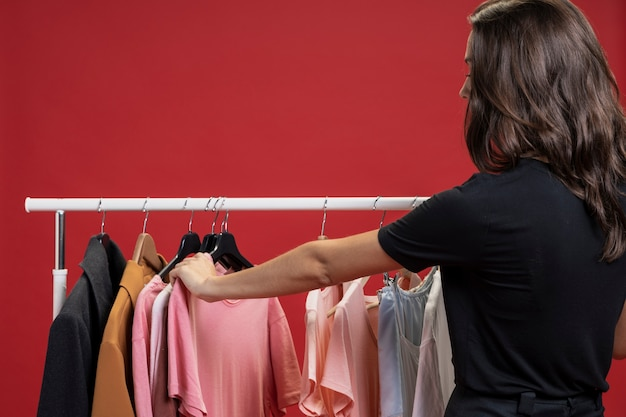 Vista lateral mulher olhando através de camisetas